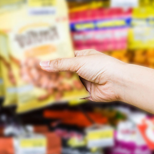 Hand reaching for a bag of snacks.