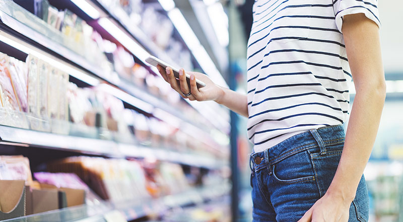 Young woman shopping healthy food in supermarket blur background