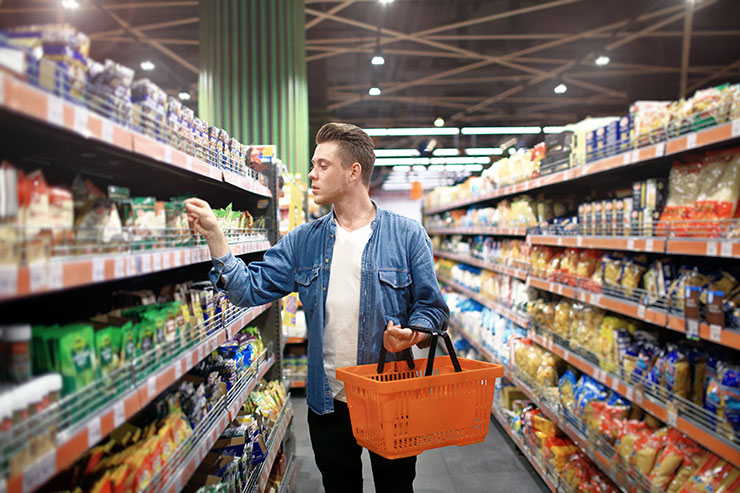 Male shopper walking through grocery store.