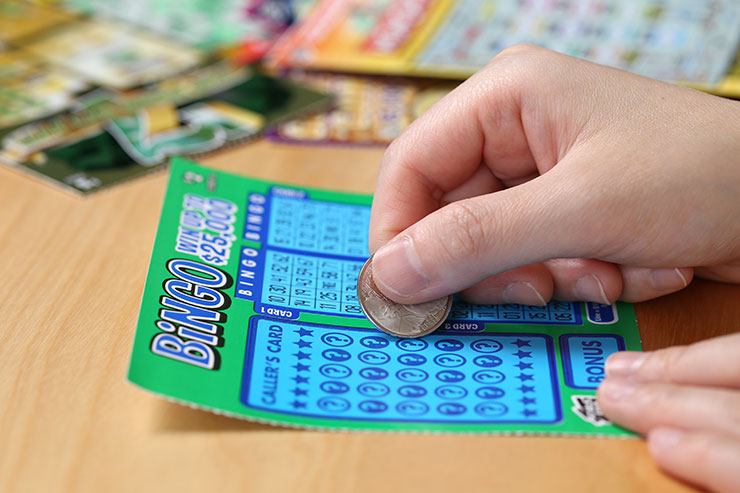 Hand holding coin to green and blue scratch-off ticket with additional scratch-off tickets in background.