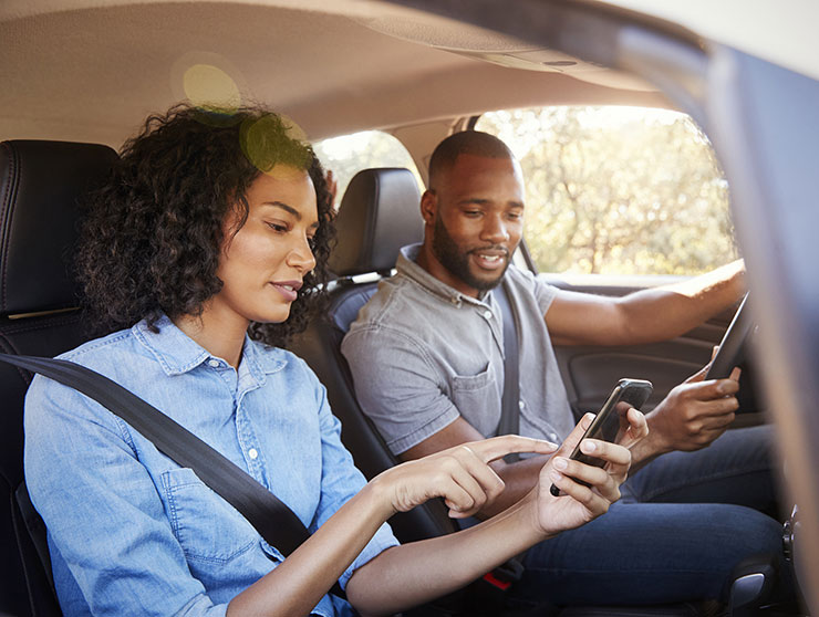 Couple in a car using smartphones