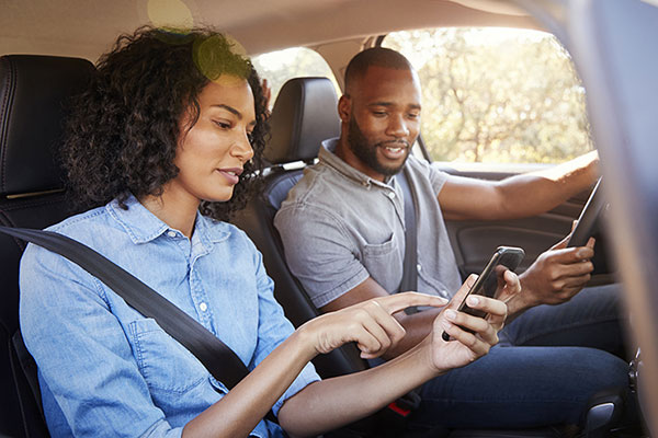 Couple in a car using smartphones.